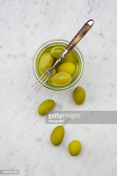 Preserving jar of pickled green olives and a fork on white marble, elevated view