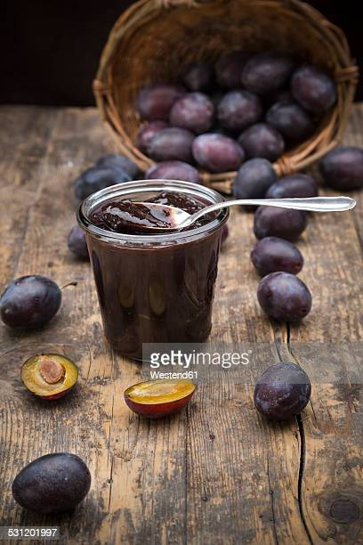 Preserving jar of plum jam and plums on wooden table