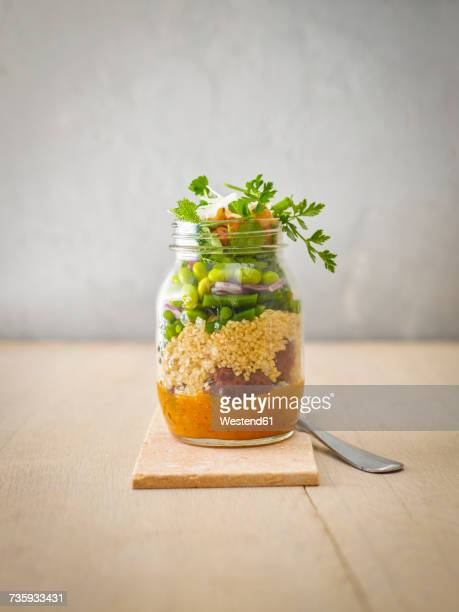 Preserving jar of quinoa salad with vegetables, coconut chips and meat balls