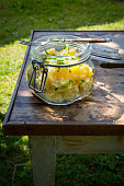 Preserving jar of Swabian potato salad and fork on wooden table in the garden
