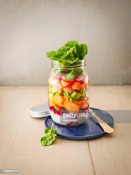 Preserving jar of various vegetables with salmon