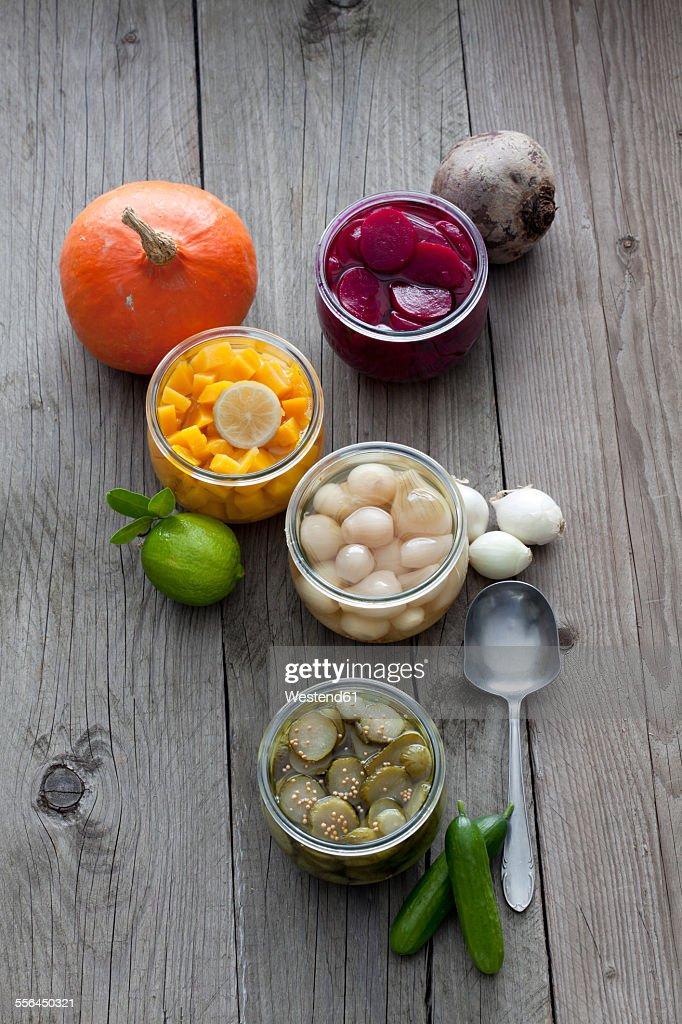 Preserving jars of different pickled vegetables