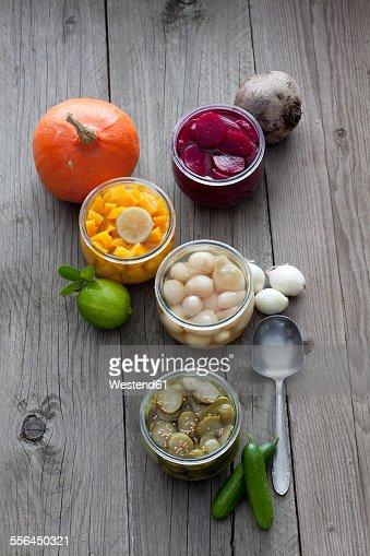 Preserving jars of different pickled vegetables
