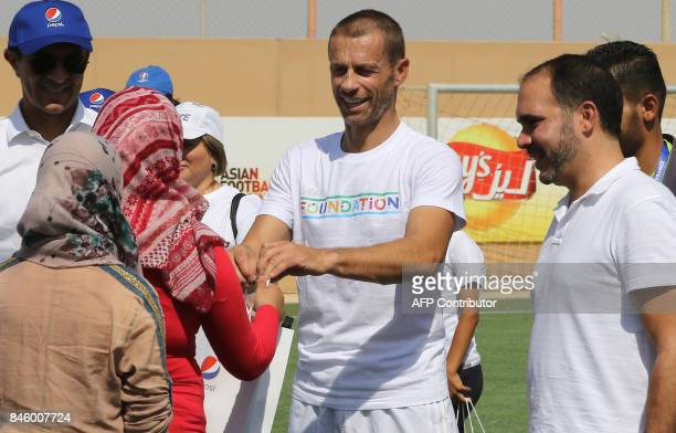 President Aleksander Ceferin and Jordan's Prince Ali bin alHussein greet children as they attend the opening ceremony of a new football field at the...