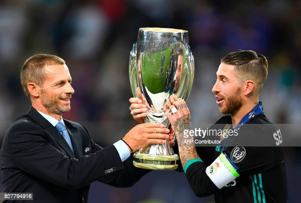 President Aleksander Ceferin gives the trophy to Real Madrid's Spanish defender Sergio Ramos after the UEFA Super Cup football match between Real...