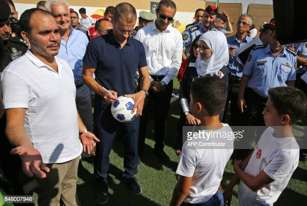 President Aleksander Ceferin signs a ball next to Jordan's Prince Ali bin alHussein as they attend the opening ceremony of a football field at the...