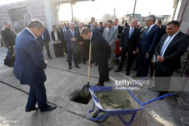 President Aleksander Ceferin throws cement with a shovel after first brick was laid during the groundbreaking ceremony of the Football Academy with...