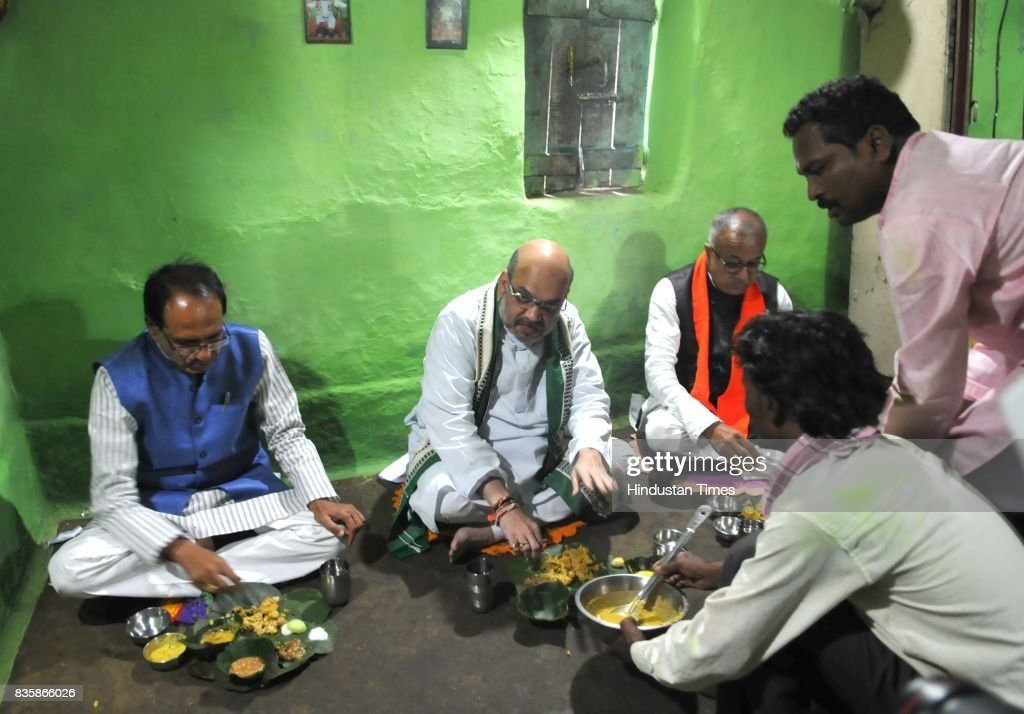 BJP President Amit Shah along with Chief Minister Shivraj Singh Chouhan having lunch at the residence of tribal Kamal Singh Uike, who belongs to Gond tribal community, on August 20, 2017 in Bhopal, India. Shah had lunch at the residence of a tribal worker as part of the BJP's outreach programme to strengthen the bond with the socially-oppressed classes.