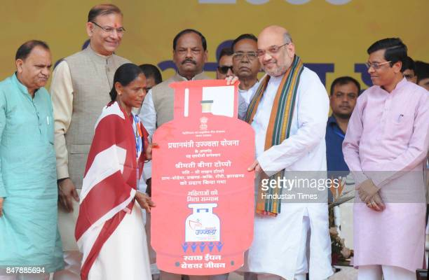 President Amit Shah giving allotments to the beneficiaries of different developments projects while Chief Minister Raghubr Das looks on during the...