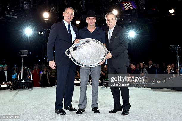 President and CEO of BMI Mike O'Neill and Vice President Writer/Publisher Relations at BMI Jody Williams present the Presidents Award to Kenny...