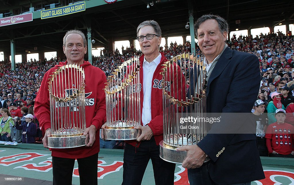 President and CEO of the Boston Red Sox Larry Lucchino, (left), Red Sox principal own John Henry (center), and Red Sox chairmanTom Werner show off the World Series trophies to the crowd at Fenway Park before the Red Sox players board the duck boats for the World Series victory parade for the Boston Red Sox on November 2, 2013 in Boston, Massachusetts.