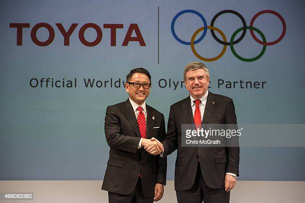 President and CEO of Toyota Motor Corporation Akio Toyoda and President of the International Olympic Committee Thomas Bach pose for photographers...