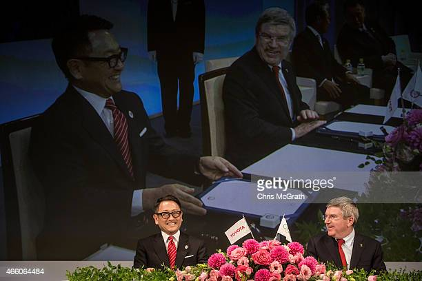President and CEO of Toyota Motor Corporation Akio Toyoda and President of the International Olympic Committee Thomas Bach joke around s they sign...