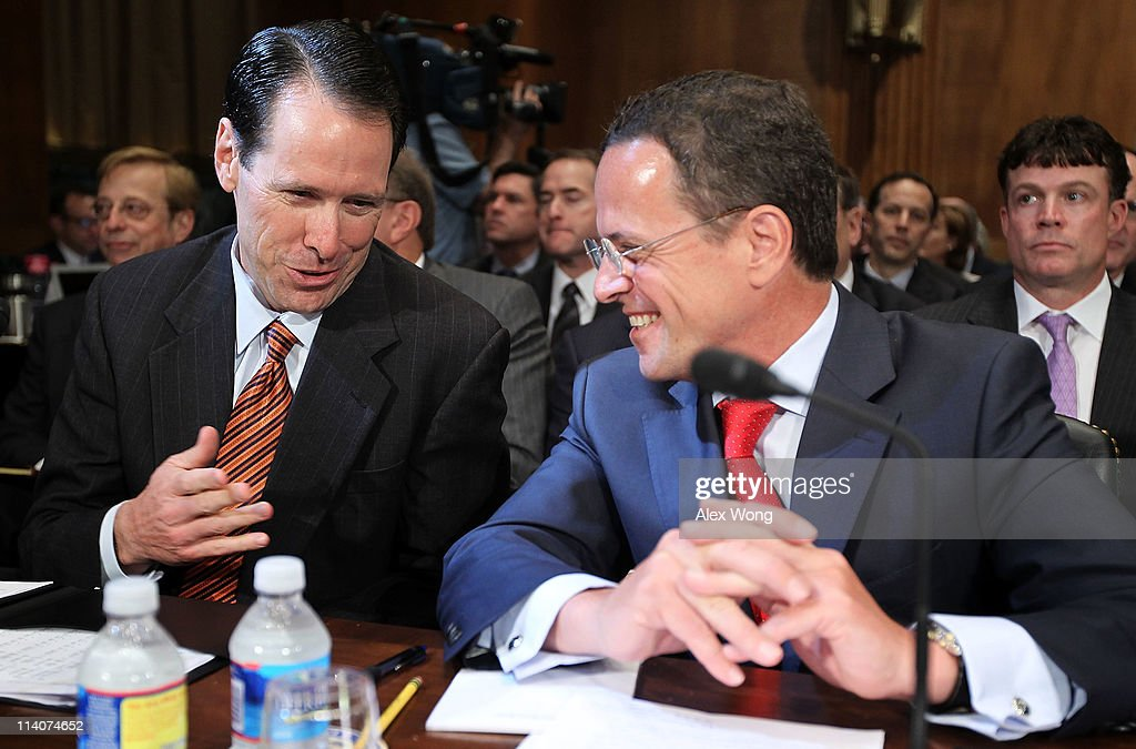 President and CEO Randall Stephenson talks to TMobile USA President and CEO Philipp Humm as they wait for the beginning of a hearing before the...