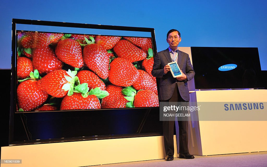 President and CEO Samsung Southwest Asia, BD Park poses beside the F8000 LED TV as he holds a Galaxy Note 510 during a launch at the Samsung Forum press conference in Hyderabad on March 1, 2013. Samsung Electronics unveiled new products and services at its Southwest Asia Forum 2013. In 2012 Samsung Electronics acheived record sales of approximately 200 billion US dollars in Southwest Asia. AFP PHOTO / Noah SEELAM