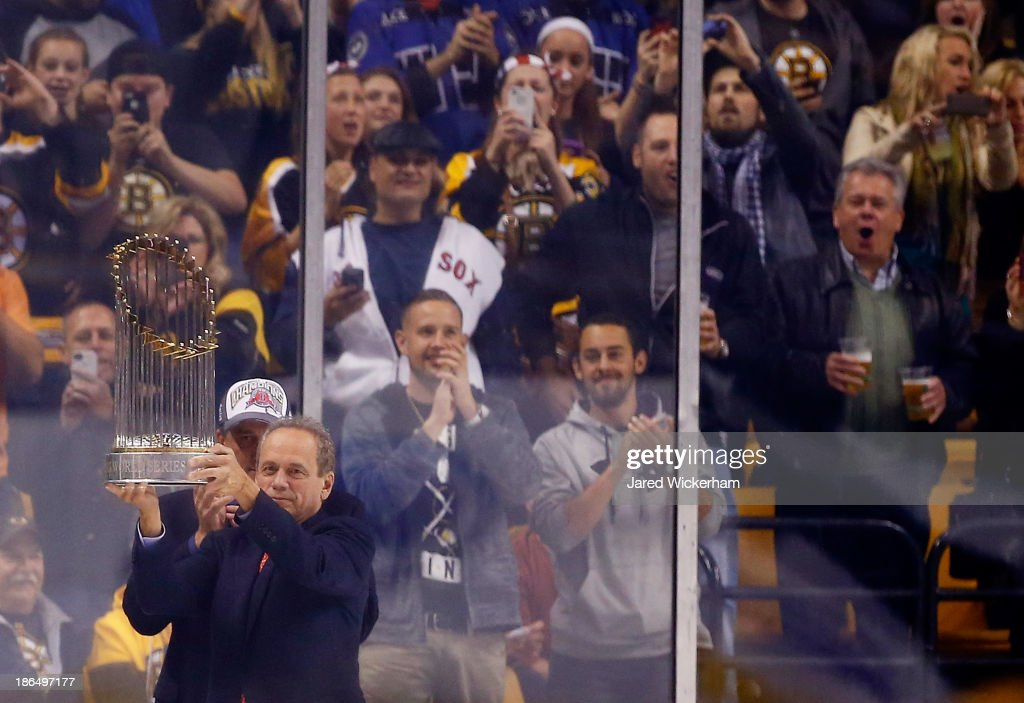 President and Chief Exective Officer Larry Lucchino of the Boston Red Sox raises the World Series trophy at TD Garden during the game between the Boston Bruins and the Anaheim Ducks on October 31, 2013 in Boston, Massachusetts.