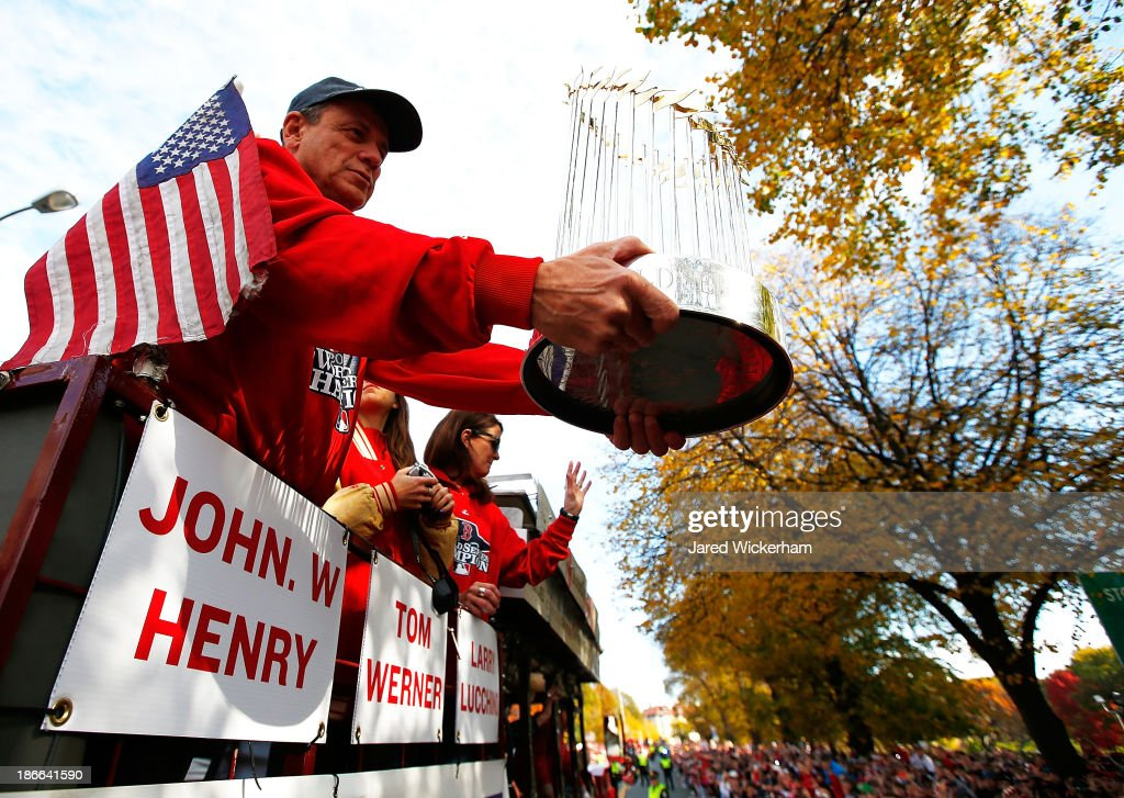 President and Chief Exective Officer Larry Lucchino of the Boston Red Sox holds up the World Series trophy during the World Series victory parade on November 2, 2013 in Boston, Massachusetts.
