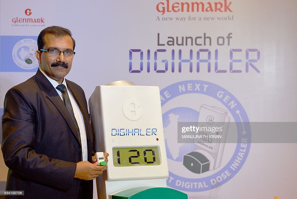 President and Head of the India Formulations and Africa Region at Glenmak Pharmaceuticals Sujesh Vasudevan poses with a model of Glenmark's 'Digihaler', India's first Digital Dose Inhaler (DDI) for Asthma and Chronic Obstructive Pulmonary Disease (COPD) in Bangalore on May 25, 2016. / AFP / Manjunath Kiran