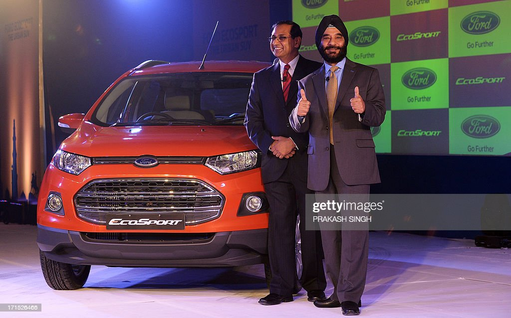 President and Managing Director of Ford India, Joginder Singh (R), and Vinay Piparsania, Executive Director for Marketing Sales and service, pose with newly launched Ford EcoSport in New Delhi on June 26, 2013. Car sales in India slid by over 12 percent in May, data showed, marking an unprecedented seventh straight month of decline, and an industry body warned that layoffs loomed in the once-booming sector. AFP PHOTO/ Prakash SINGH