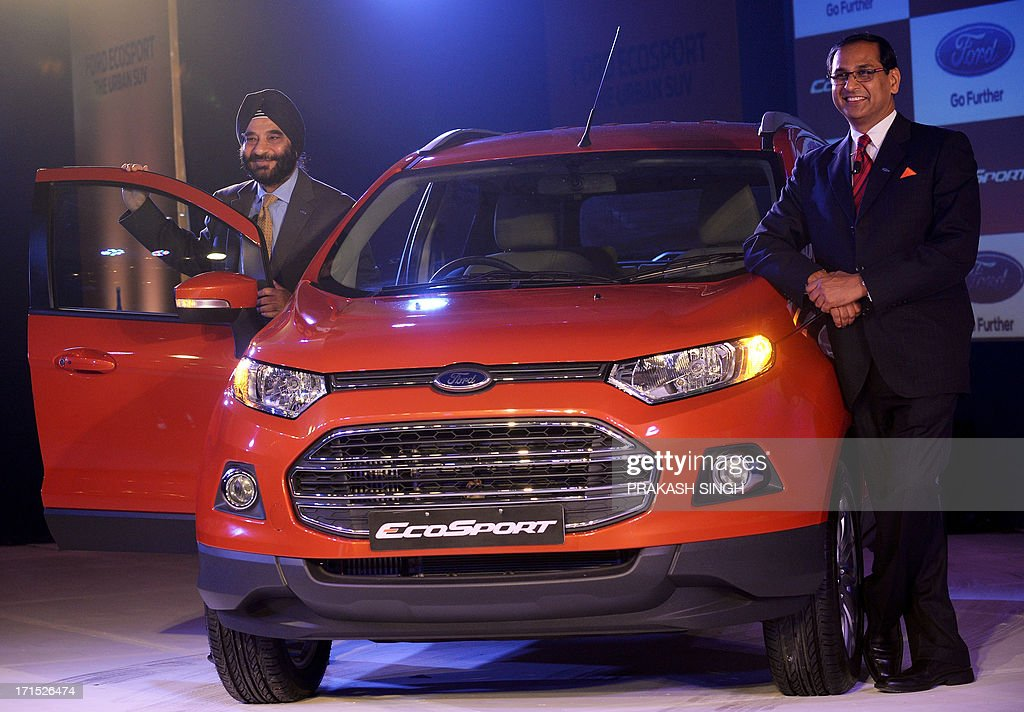 President and Managing Director of Ford India, Joginder Singh (L), and Vinay Piparsania, Executive Director for Marketing Sales and service, pose with newly launched Ford EcoSport in New Delhi on June 26, 2013. Car sales in India slid by over 12 percent in May, data showed, marking an unprecedented seventh straight month of decline, and an industry body warned that layoffs loomed in the once-booming sector. AFP PHOTO/ Prakash SINGH