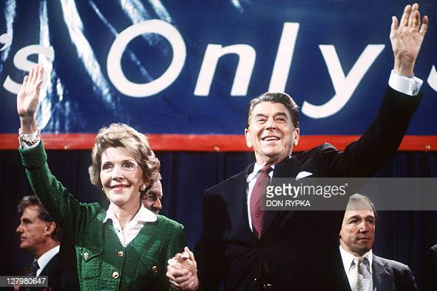 US President and Republican presidential candidate Ronald Reagan and his wife Nancy wave to supporters at an electoral meeting in November 1984 a few...