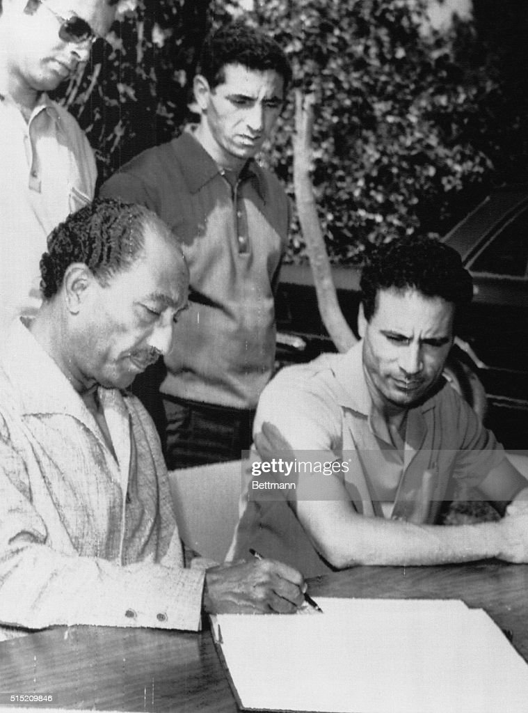 President Anwar Sadat (L) and Libyan leader Colonel Muammar al-Qaddafi (R) look over communiqué upon conclusion of three days of talks here 8/29. Sadat and al-Qaddafi, in a last minute compromise, agreed to merge their two countries by stages, a joint announcement on Cairo Radio said 8/29.