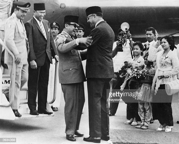 President Ayub Khan of Pakistan greeting President Sukarno of Indonesia at the foor of the aircraft as he arrives at Karachi Airport for his official...