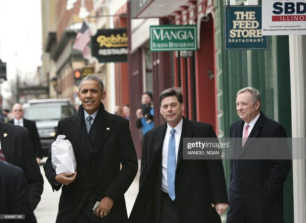 US President Barack carries his lunch from the Feed Store restaurant near the Old State Capitol in Springfield, Illinois on February 10, 2016. / AFP / Mandel Ngan