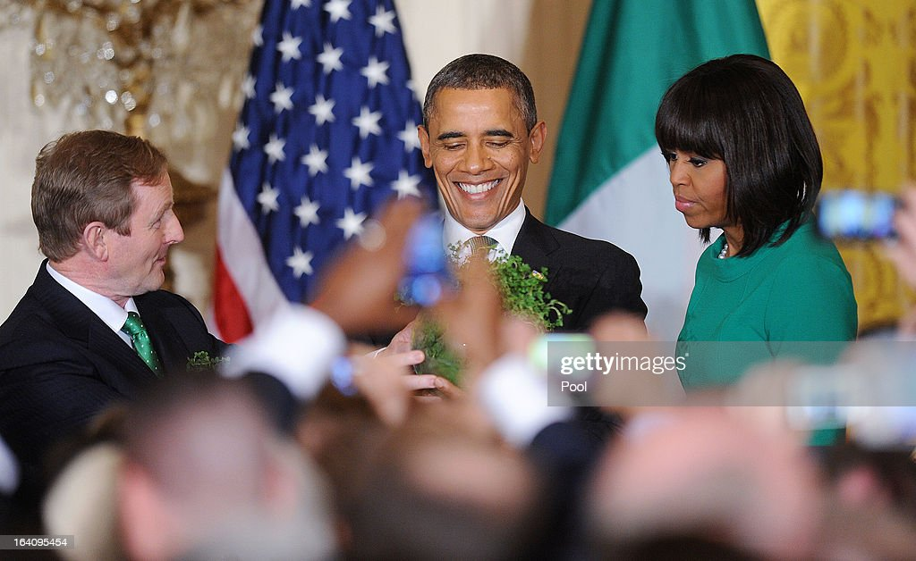 U.S. President Barack Obama (C) accepts a bowl of shamrocks from Irish Prime Minister Enda Kenny (L), while first lady Michelle Obama looks on during a reception in the East Room of the White House on March 19, 2013 in Washington, DC. President Obama met with Irish Prime Minister Enda Kenny prior to the annual St. Patrick's Day lunch hosted at the Capitol.