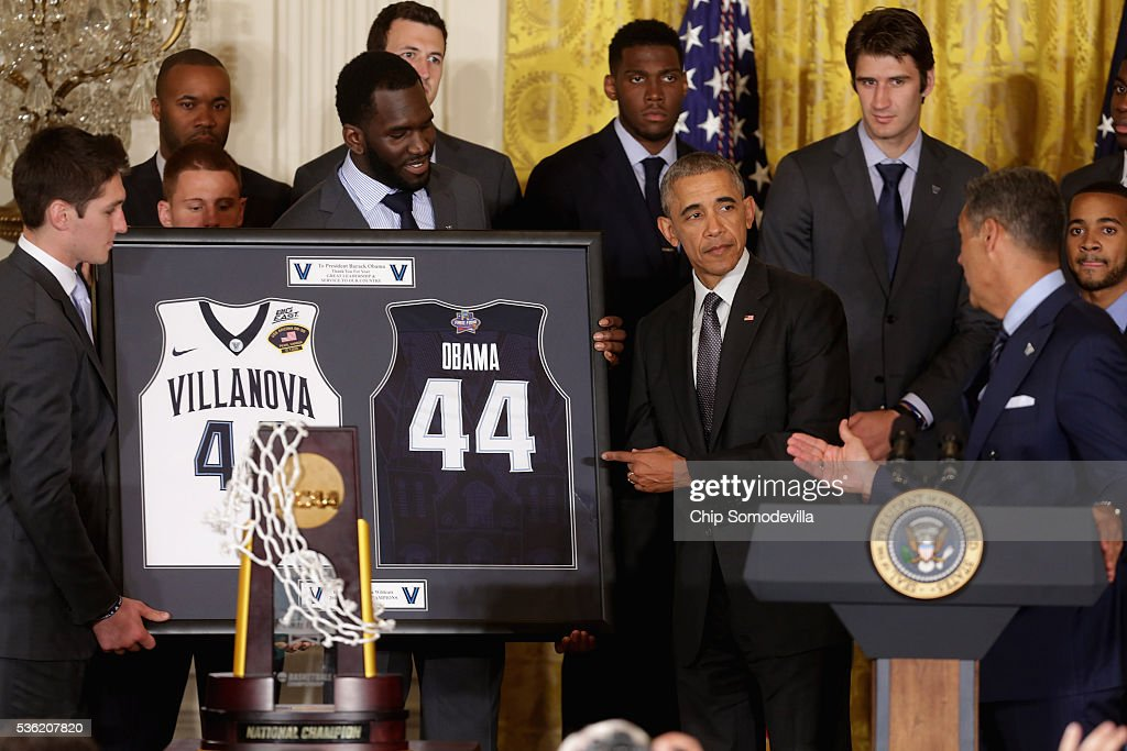 U.S. President Barack Obama (4th R) accepts framed uniforms from NCAA 2016 National Champions Villanova University's men's basketball team players Daniel Ochefu (C) and Ryan Arcidiacono (L) in the East Room of the White House May 31, 2016 in Washington, DC. Obama said that although he did not pick the Wildcats to win the championship that the final game against the University of North Carolina was one of the greatest of college basketball history.