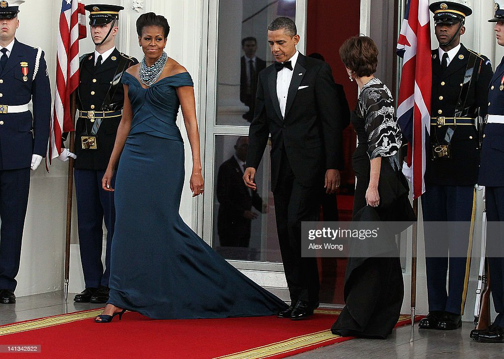 U.S. President <a gi-track='captionPersonalityLinkClicked' href=/galleries/search?phrase=Barack+Obama&family=editorial&specificpeople=203260 ng-click='$event.stopPropagation()'>Barack Obama</a> (C) accidentially steps on First lady <a gi-track='captionPersonalityLinkClicked' href=/galleries/search?phrase=Michelle+Obama&family=editorial&specificpeople=2528864 ng-click='$event.stopPropagation()'>Michelle Obama</a>'s dress as they walk onto the North Portico before the arrival of British Prime Minister David Cameron and his wife <a gi-track='captionPersonalityLinkClicked' href=/galleries/search?phrase=Samantha+Cameron&family=editorial&specificpeople=624344 ng-click='$event.stopPropagation()'>Samantha Cameron</a> the White House March 14, 2012 in Washington, DC. Cameron is on a three-day visit to the U.S. and he was expected to have talks with Obama on the situations in Afghanistan, Syria and Iran.
