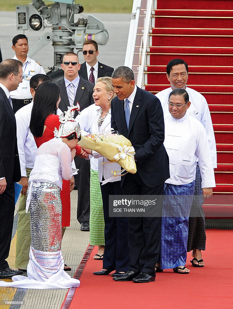 US President Barack Obama (C), accompanied by Secretary of State Hillary Clinton, receives a bunch of flowers from a girl on arrival at the Yangon International airport on November 19, 2012. Obama arrived in Myanmar for a historic visit aimed at encouraging a string of dramatic political reforms in the former pariah state. AFP PHOTO/ Soe Than WIN