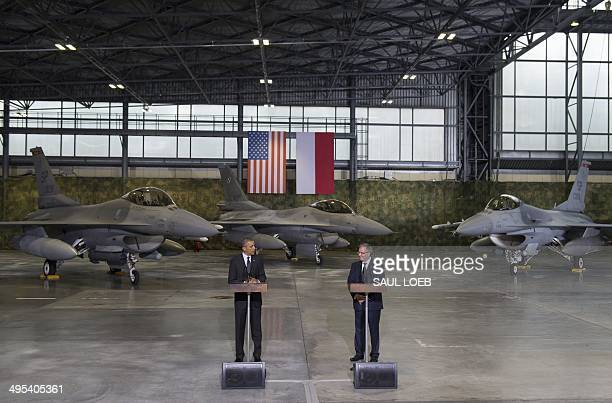 US President Barack Obama addresses US and Polish airmen next to Polish President Bronislaw Komorowski in front of F16 fighter jets in a hangar at...