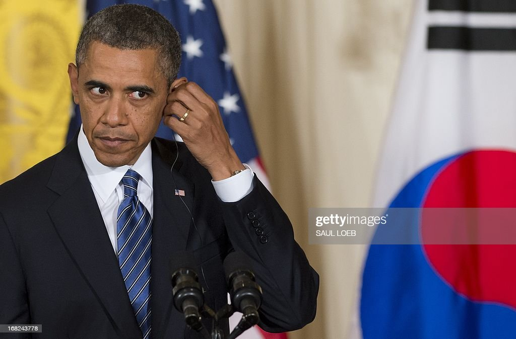 US President Barack Obama adjusts his translation ear piece during a joint press conference with South Korean President Park Geun-hye in the East Room of the White House in Washington on May 7, 2013. AFP PHOTO / Saul LOEB