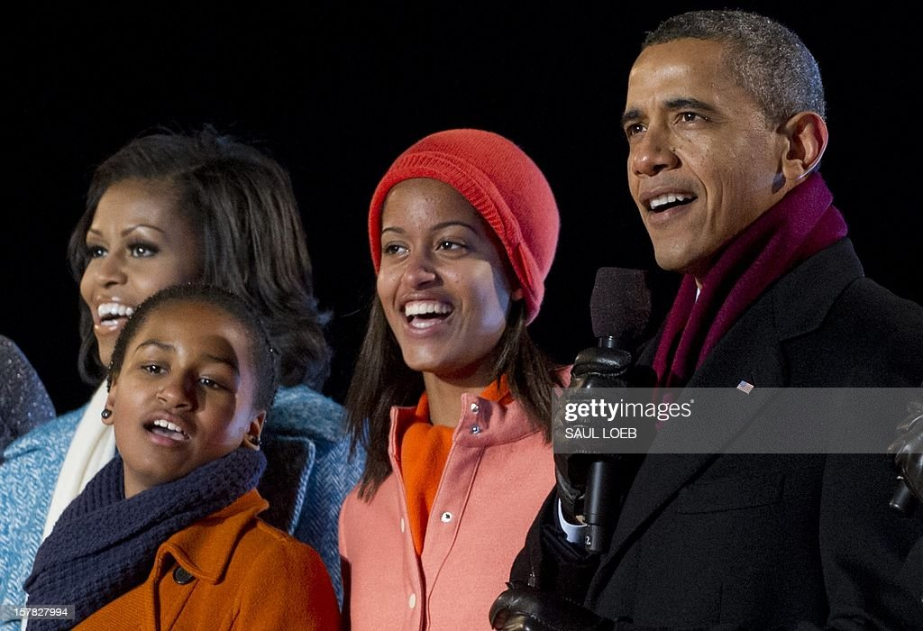 US President Barack Obama alongside First Lady Michelle Obama and daughters Sasha (2nd L) and Malia (2nd R), sing during the National Christmas Tree Lighting on the Ellipse adjacent to the White House in Washington, DC, on December 6, 2012. The annual event, hosted by Harris, features US President Barack Obama and performances by Jason Mraz, Ledisi, James Taylor, Kenny 'Babyface' Edmonds, Colbie Caillat and American Idol season 11 winner Phillip Phillips. AFP PHOTO / Saul LOEB