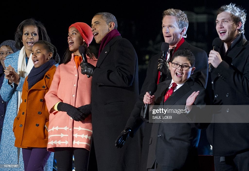 US President Barack Obama (C) alongside First Lady Michelle Obama (2nd L), Marian Robinson (L), daughters Sasha (3rd L) and Malia, sing with actor Neil Patrick Harris (3rd R), actor Rico Rodriguez (2nd R) from the televison show 'Modern Family' and American Idol season 11 winner Phillip Phillips (R) during the National Christmas Tree Lighting on the Ellipse adjacent to the White House in Washington, DC, on December 6, 2012. The annual event, hosted by Harris, features US President Barack Obama and performances by Jason Mraz, Ledisi, James Taylor, Kenny 'Babyface' Edmonds, Colbie Caillat and American Idol season 11 winner Phillip Phillips. AFP PHOTO / Saul LOEB