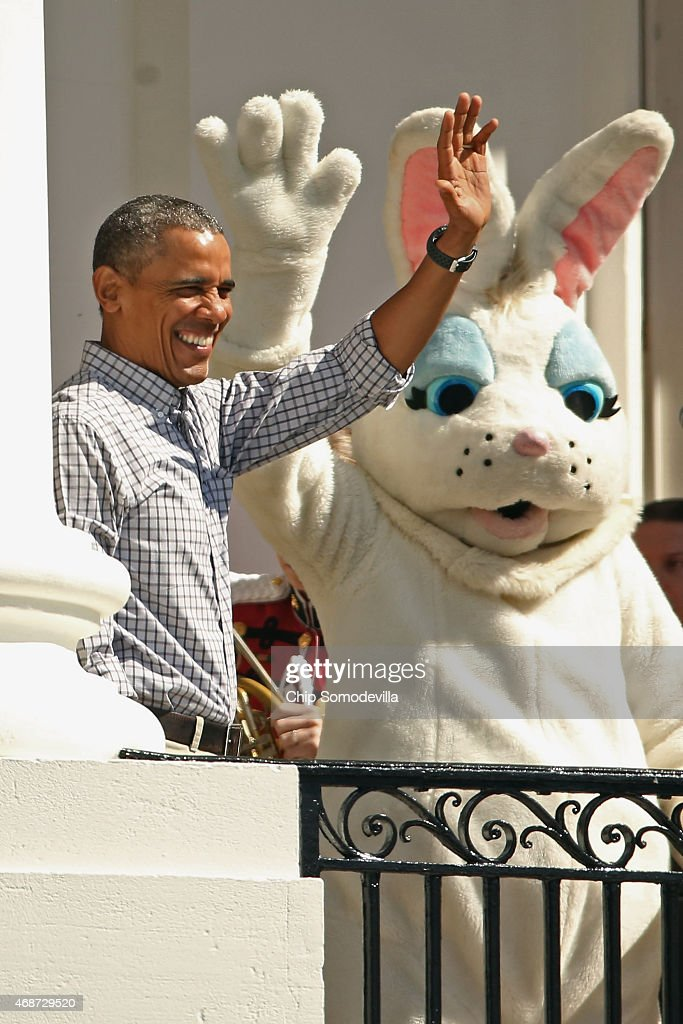 President Barack Obama and a person dressed as the Easter Bunny wave to visitors from the Truman Balcony during the White House Easter Egg Roll on...