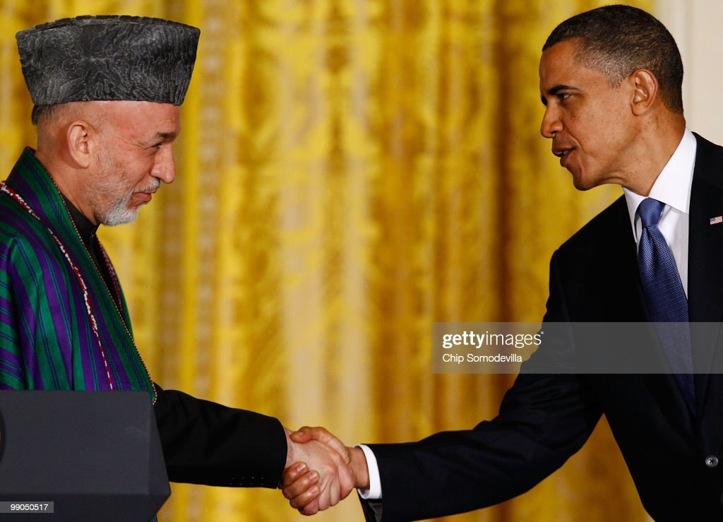 S President Barack Obama and Afghanistan President Hamid Karzai shake hands during a joint news conference in the East Room of the White House May 12...