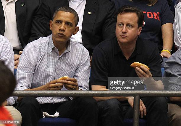 S President Barack Obama and British Prime Minister David Cameron eat a hot dog as they watch the first half at UD Arena as the Western Kentucky...