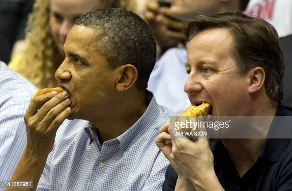 US President Barack Obama and British Prime Minister David Cameron eat hot dogs as they sit in the stands at University of Dayton Arena in Dayton...