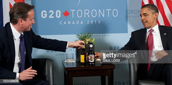 US President Barack Obama and British Prime Minister David Cameron trade bottles of beer to settle a bet on the USEngland World Cup soccer game...
