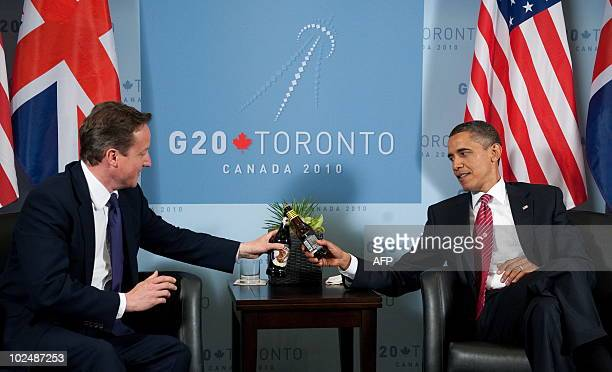 US President Barack Obama and British Prime Minister David Cameron trade bottles of beer to settle a bet on the USUK World Cup Soccer game during a...