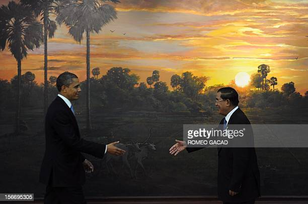 US President Barack Obama and Cambodian Prime Minister Hun Sen reach out to shake hands on arrival at the Peace Palace for the Association of...