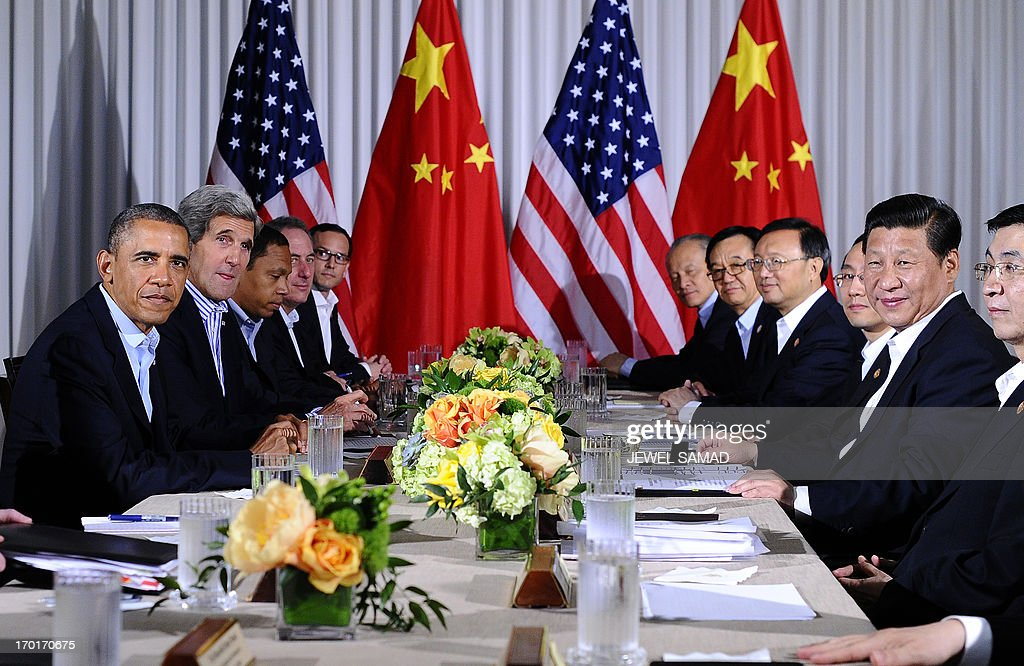 US President Barack Obama (L) and Chinese President Xi Jinping (R) along with their delegates hold a meeting at the Annenberg Retreat at Sunnylands in Rancho Mirage, California, on June 8, 2013. Obama and Xi wrap up their debut summit Saturday, grasping for a personal understanding that could ease often prickly US-China relations. Skipping the usual summit pageantry, Obama and Xi went without neckties, in a departure from the stifling formality that marked Obama's halting interactions with China's ex-president Hu Jintao. AFP PHOTO/Jewel Samad