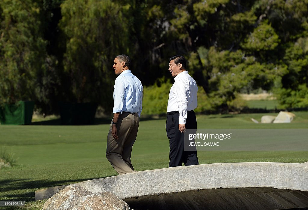 US President Barack Obama (L) and Chinese President Xi Jinping chat as they take a walk at the Annenberg Retreat at Sunnylands in Rancho Mirage, California, on June 8, 2013. Obama and Xi wrap up their debut summit Saturday, grasping for a personal understanding that could ease often prickly US-China relations. Skipping the usual summit pageantry, Obama and Xi went without neckties, in a departure from the stifling formality that marked Obama's halting interactions with China's ex-president Hu Jintao. AFP PHOTO/Jewel Samad