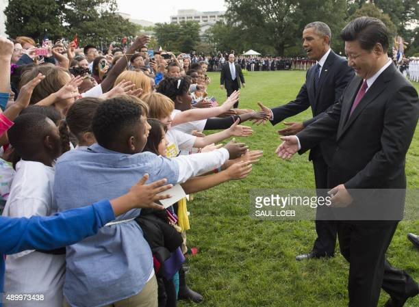 US President Barack Obama and Chinese President Xi Jinping greet school children during a State Arrival ceremony on the South Lawn of the White House...