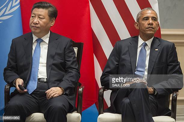 US President Barack Obama and Chinese President Xi Jinping look on after formally joining the Paris Climate deal at Ruyi Hall at the West Lake State...