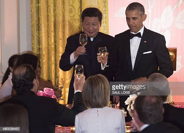 US President Barack Obama and Chinese President Xi Jinping toast during a State Dinner in the East Room of the White House in Washington DC September...