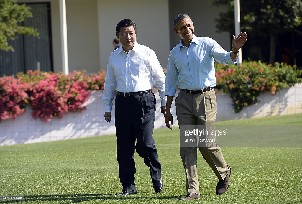 US President Barack Obama (R) and Chinese President Xi Jinping wave as they take a walk at the Annenberg Retreat at Sunnylands in Rancho Mirage, California, on June 8, 2013. Obama and Xi wrap up their debut summit Saturday, grasping for a personal understanding that could ease often prickly US-China relations. Skipping the usual summit pageantry, Obama and Xi went without neckties, in a departure from the stifling formality that marked Obama's halting interactions with China's ex-president Hu Jintao. AFP PHOTO/Jewel Samad