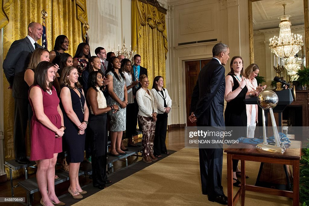 US President Barack Obama (3R) and Coach Cheryl Reeve (R) listen as Captain Lindsay Whalen (2R) speak during an event to celebrate the 2015 WNBA Champions, Minnesota Lynx, in the East Room of the White House June 27, 2016 in Washington, DC. / AFP / Brendan Smialowski